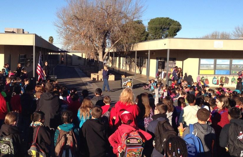 Students listening to the principal at an outside assembly