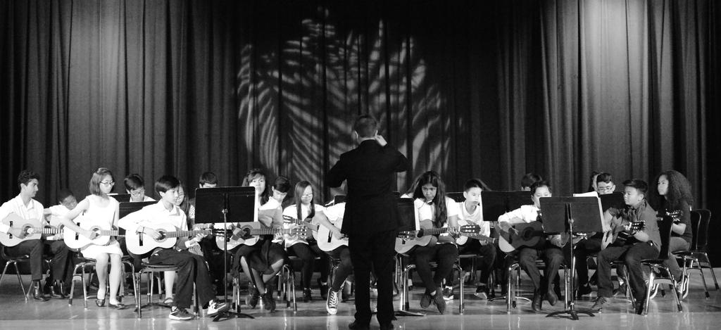Black and white photograph of CCA students playing guitar on stage.
