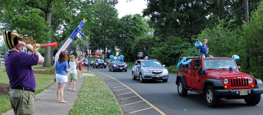 Photo of Washington principal blowing horn and teachers waving as 5th graders and families pass by during Grade 5 Clap Out Car Parade