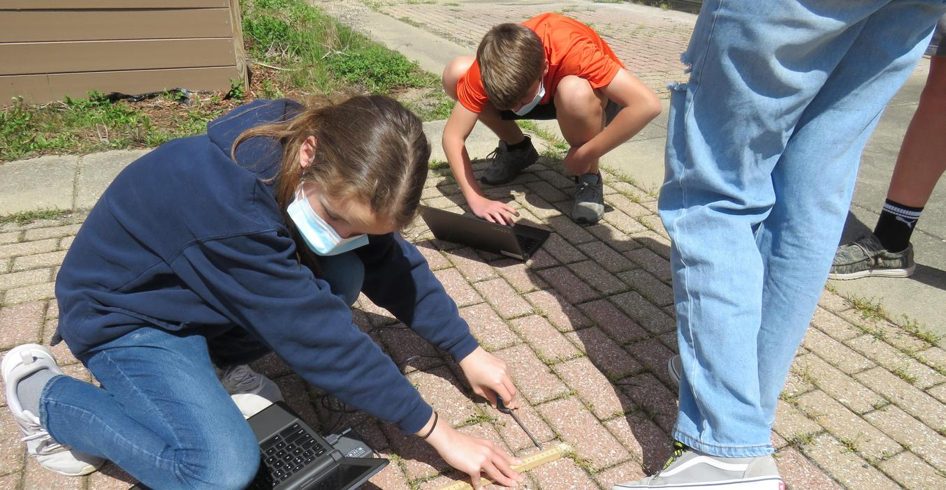 TKMS  students measure light and heat on different surfaces outside.