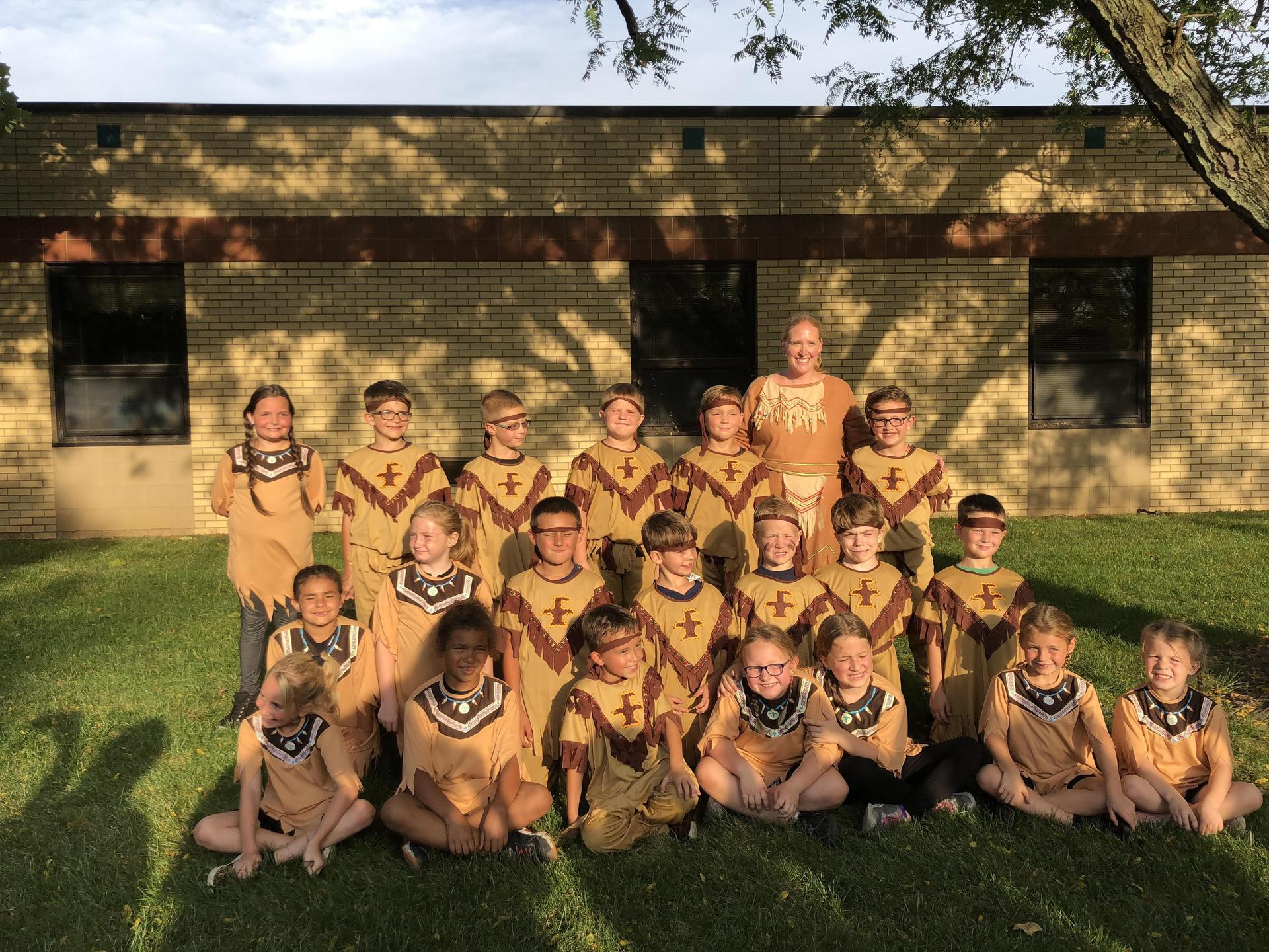 Teacher and class dressed as Native Americans.
