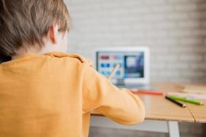 Rear view of a child working on a laptop