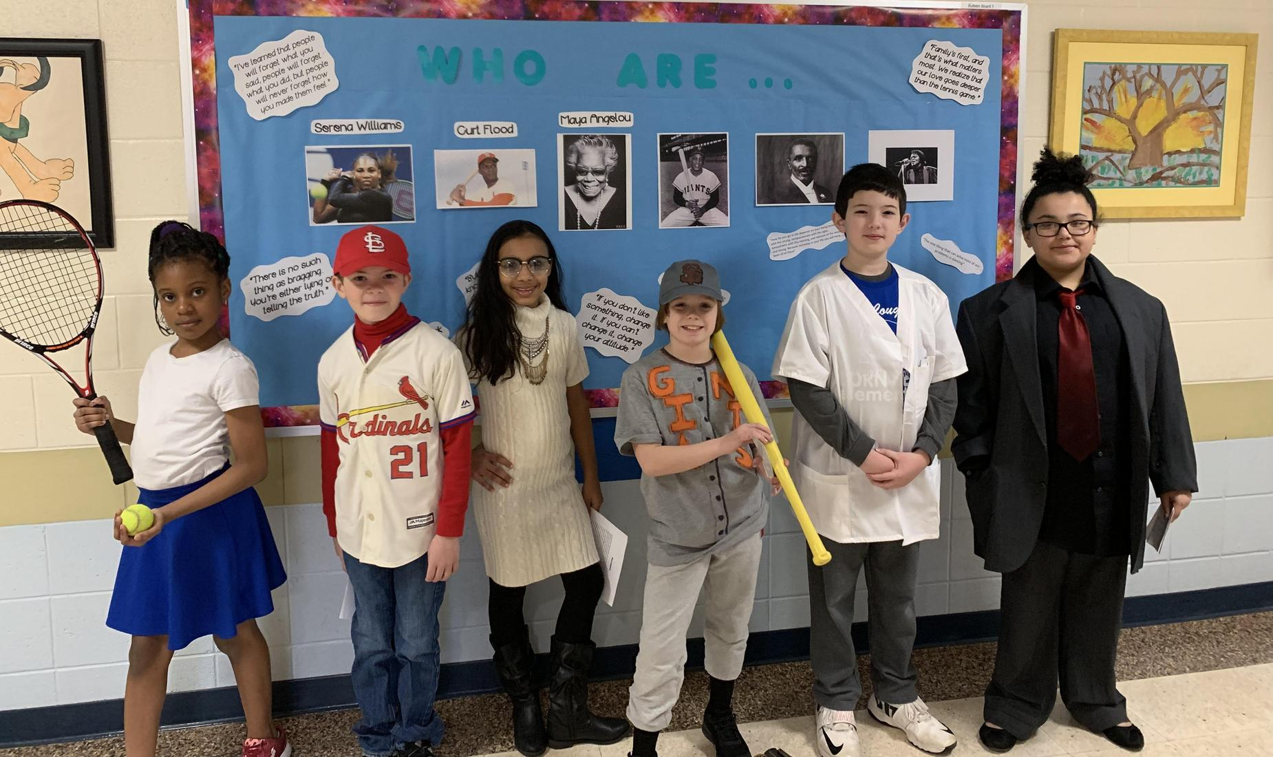 6 students pretending to be wax figures portraying famous Americans: Serena Williams; baseball player Curt Flood; Maya Angelou; Willie Mays; George Washington Carver; and James Brown.