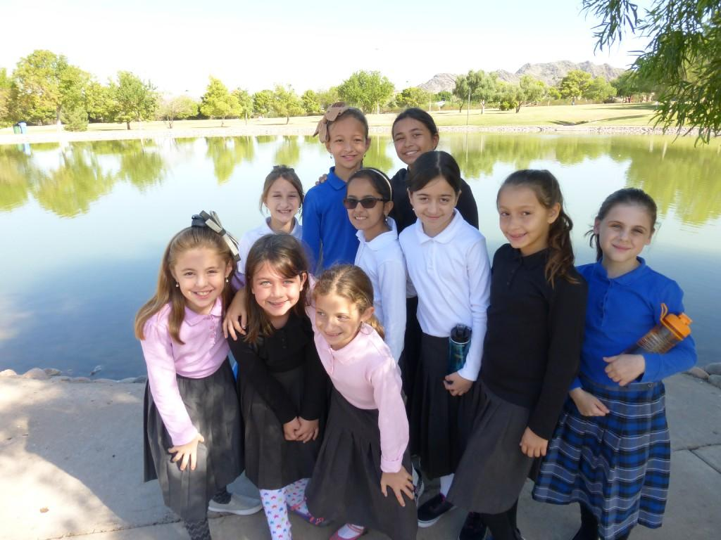 Girls smiling outside at a pond