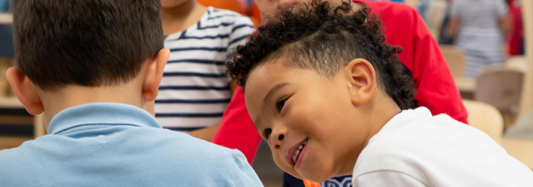 A pre-k student leaning over and smiling at another pre-k student.