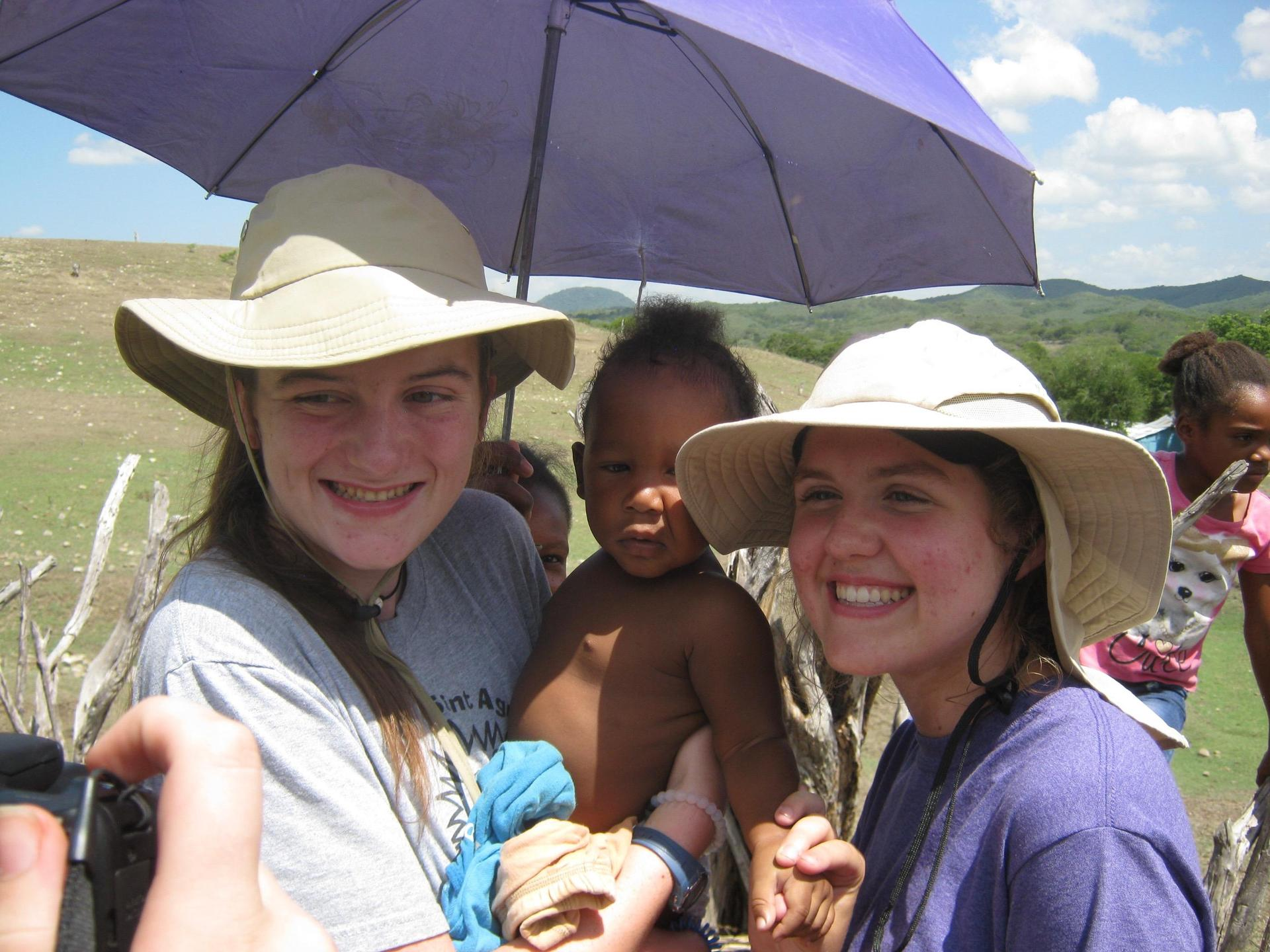Two students holding a baby while on a mission trip to Banica