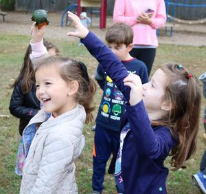 Photo of two kindergartners passing gourd during a game at the annual Pumpkin Patch.
