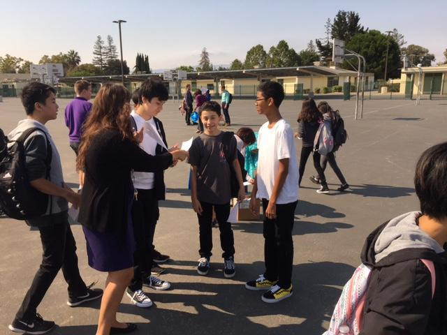 students and a teacher on outside basketball court looking at image of eclipse reflected on paper
