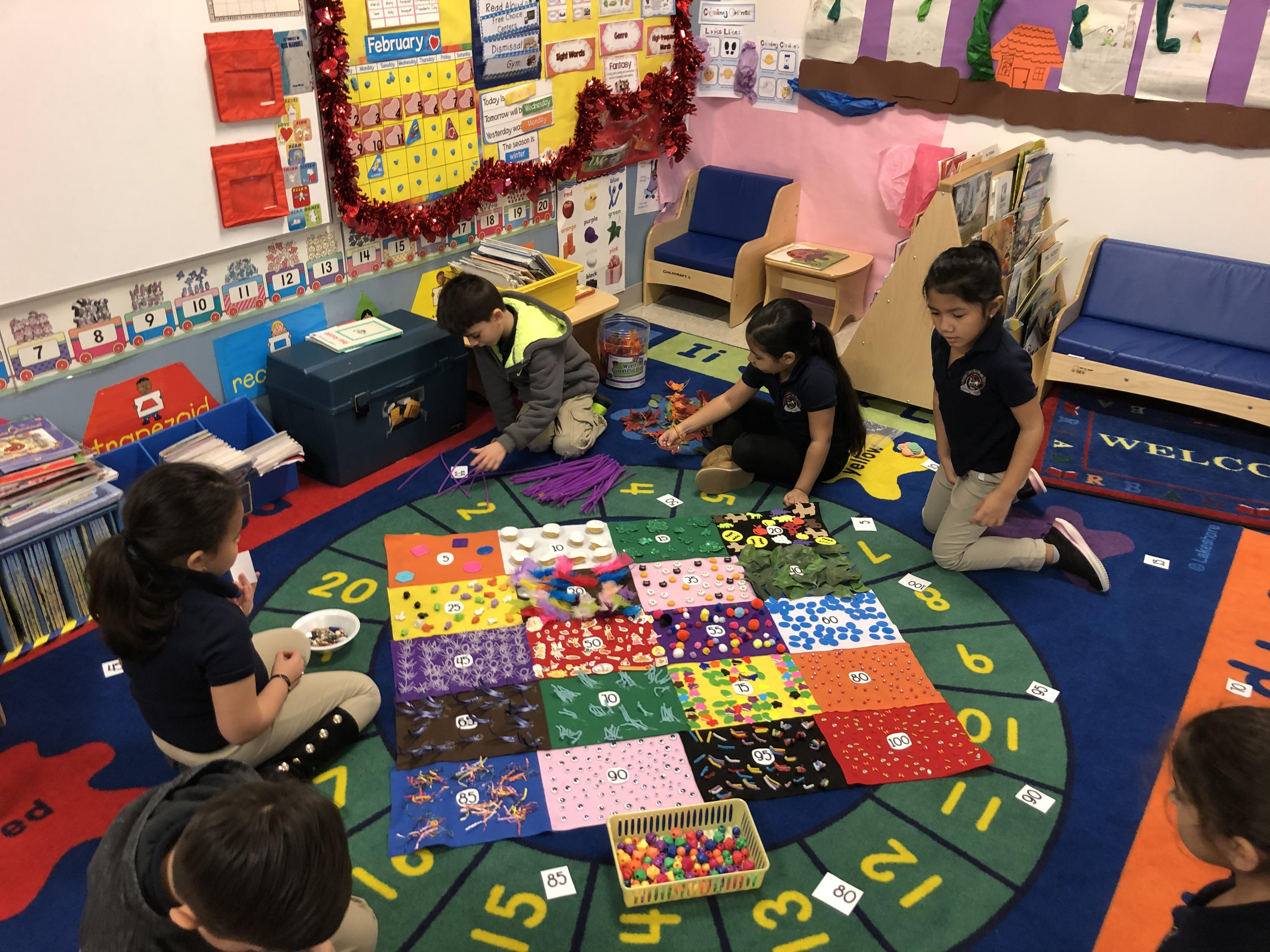 several children sitting on the class rug gathering items