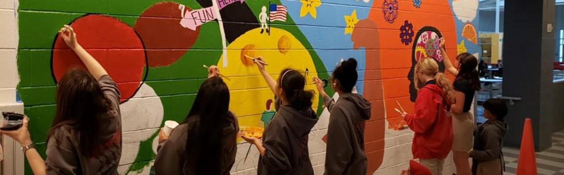 Several students painting a mural on a cinder block wall.