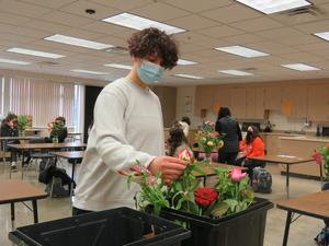 A student creates a floral arrangement during a mental wellness day activity.