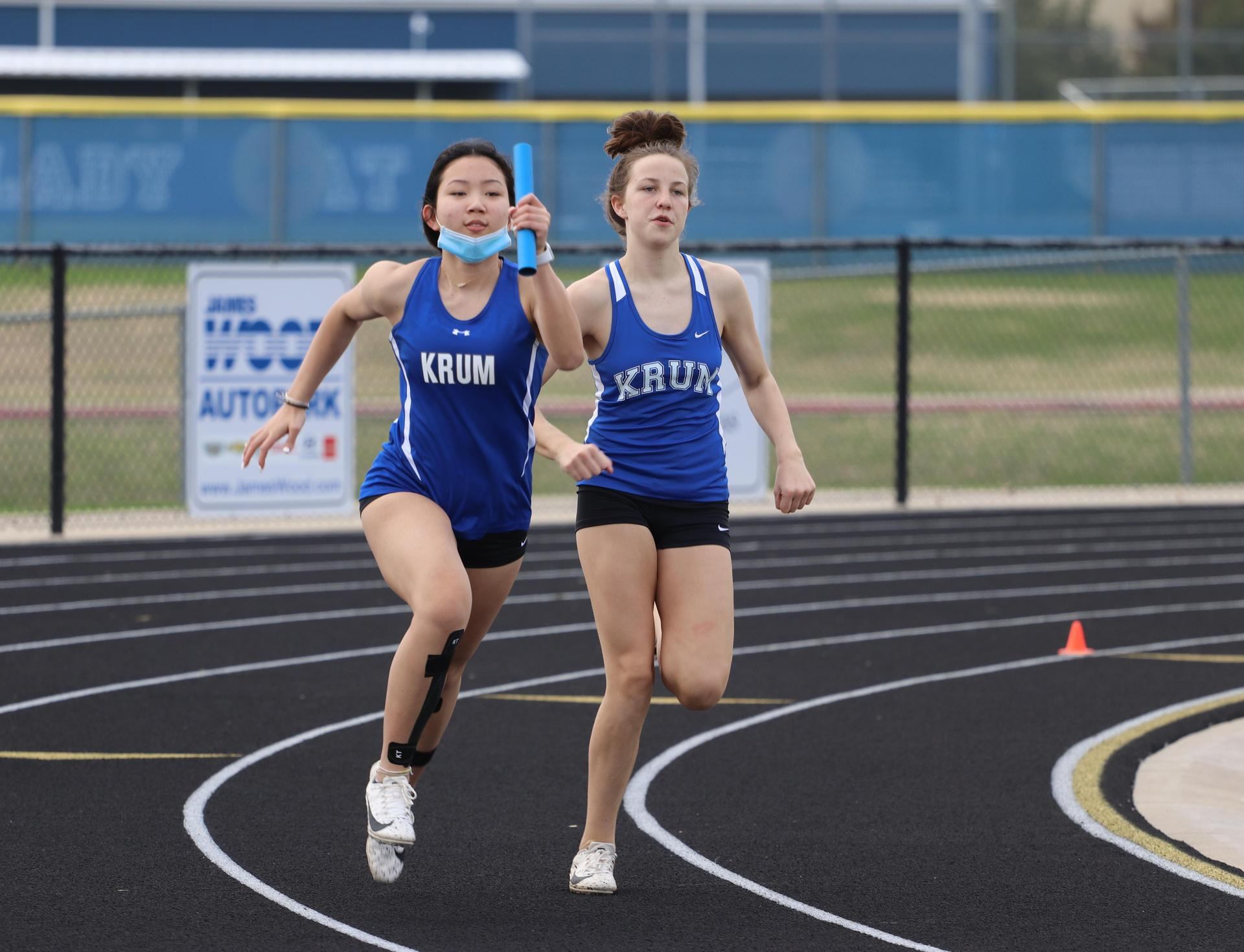 2 track athletes run in the relay