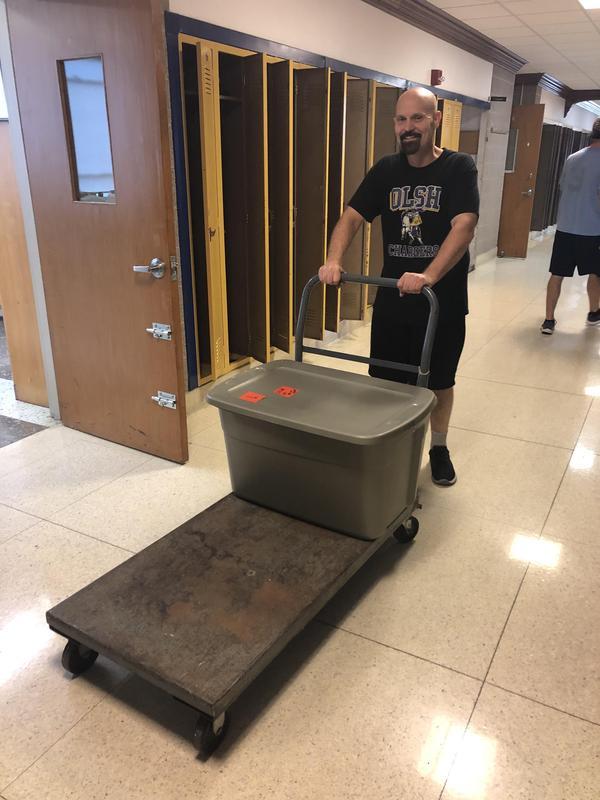 photo of teacher pushing a cart with a bin