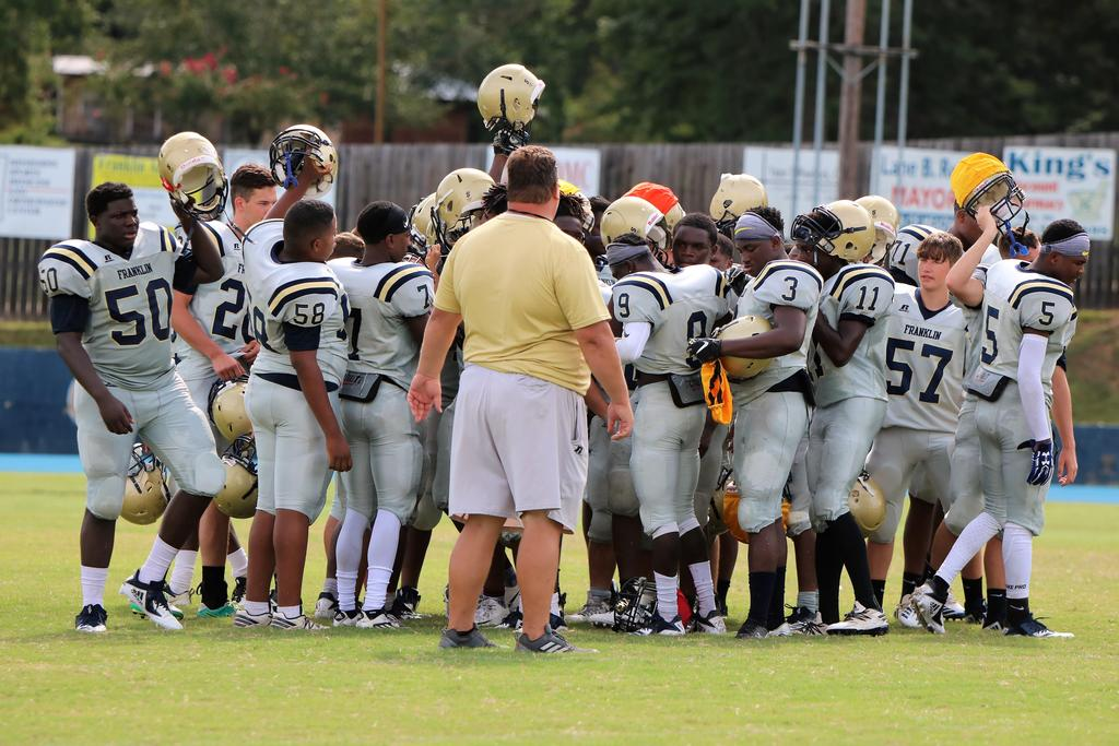 football players in huddle before the start of game