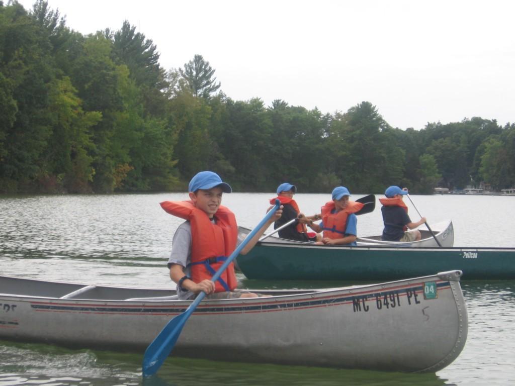 kids rowing canoe on lake