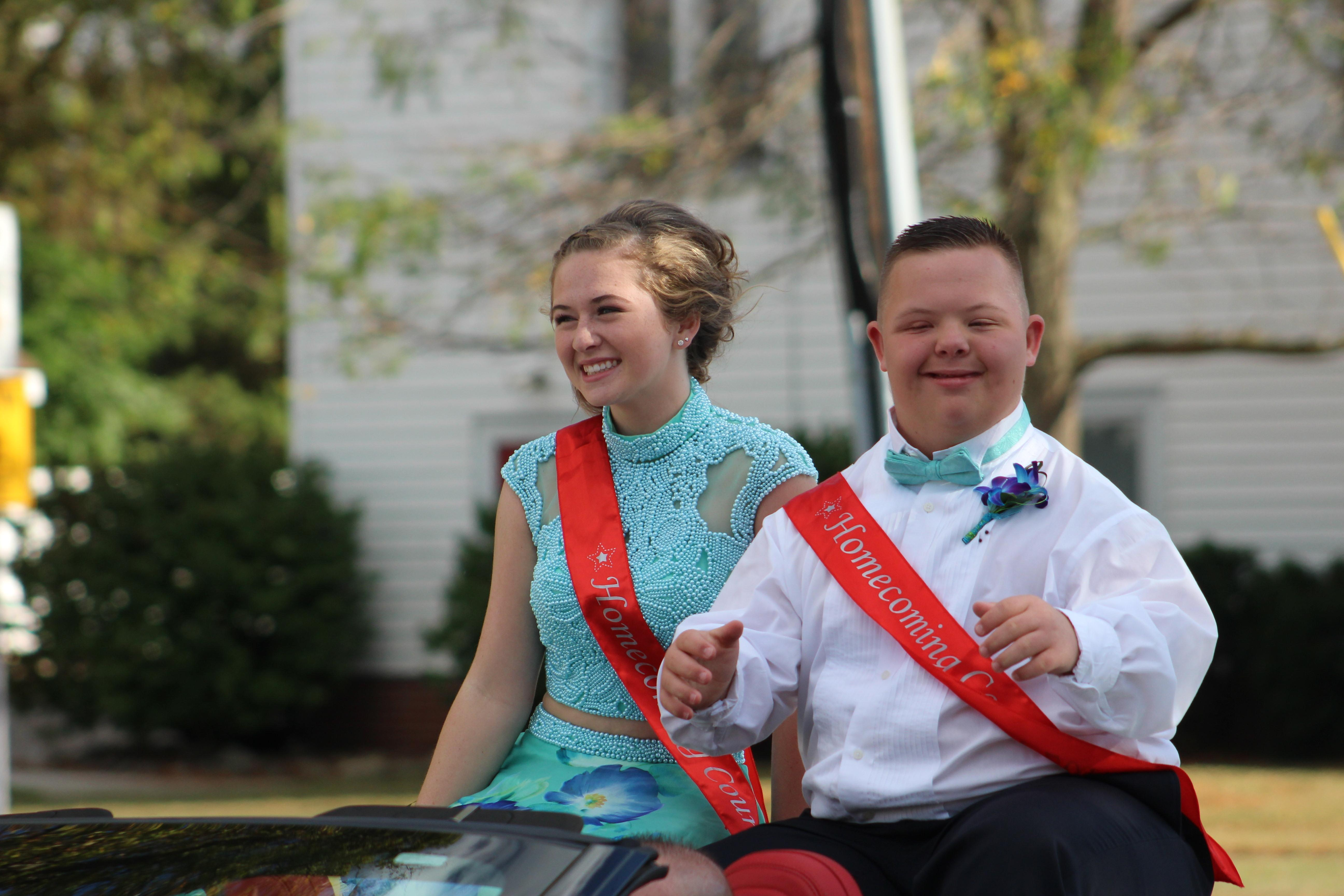Two students riding in a convertible during the homecoming parade