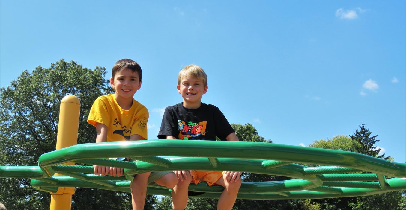 Two McFall boys sit atop the climbing bars at McFall.