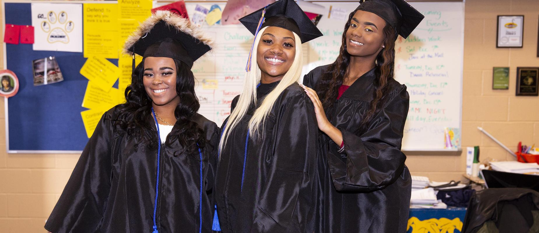 Three grads smiling