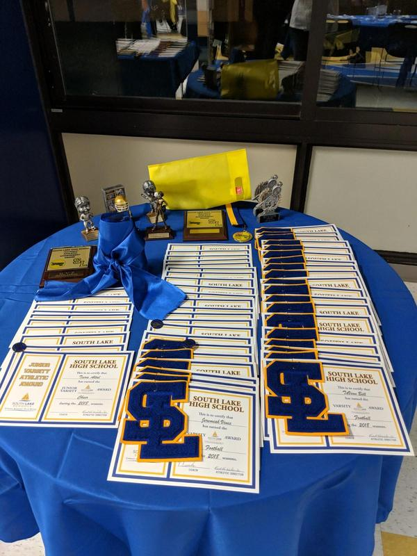 A second awards table with certificates and awards displayed