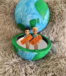 Hollow globe with 2 boy figures inside saying