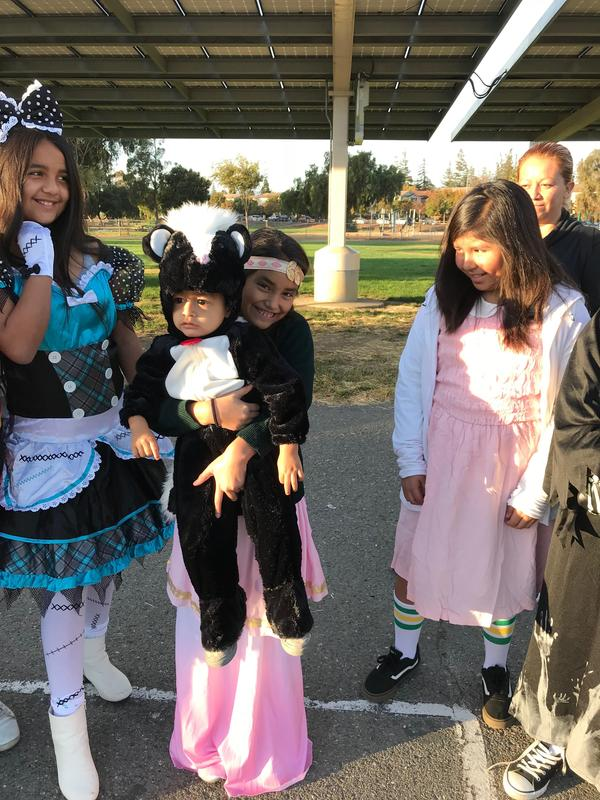 A student holding her sibling in a skunk costume