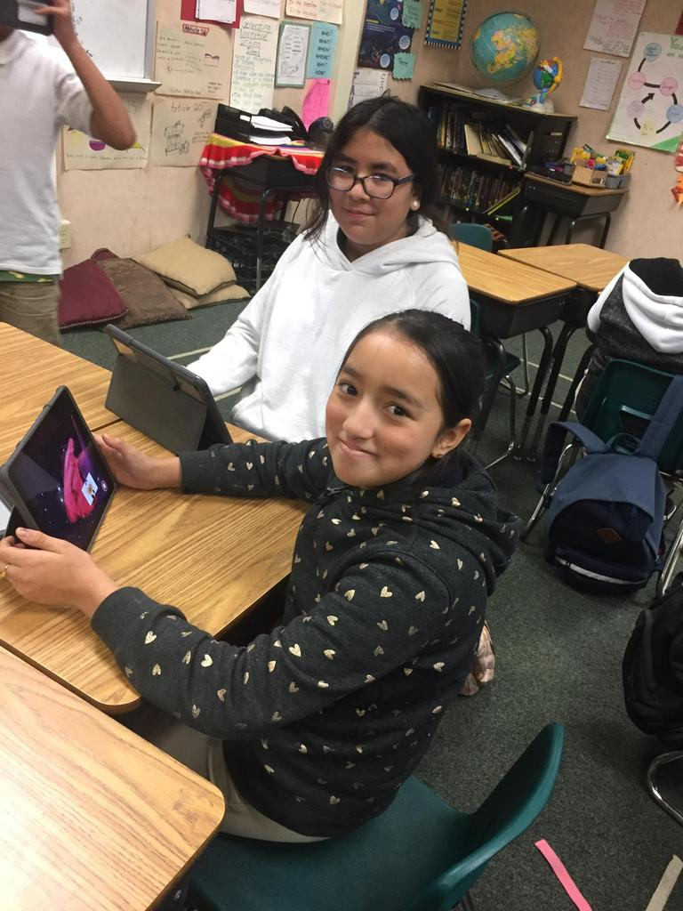 two students pose for a picture while coding on iPads
