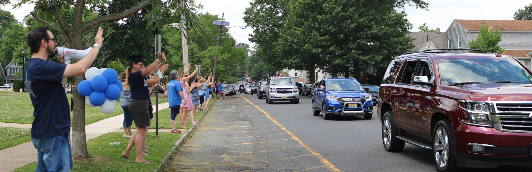 Photo of McKinley staff waving to 5th graders during Grade 5 Clap Out Car Parade.