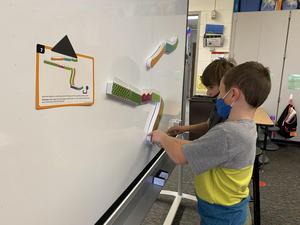 Students design and build marble runs on the magnetic white board.