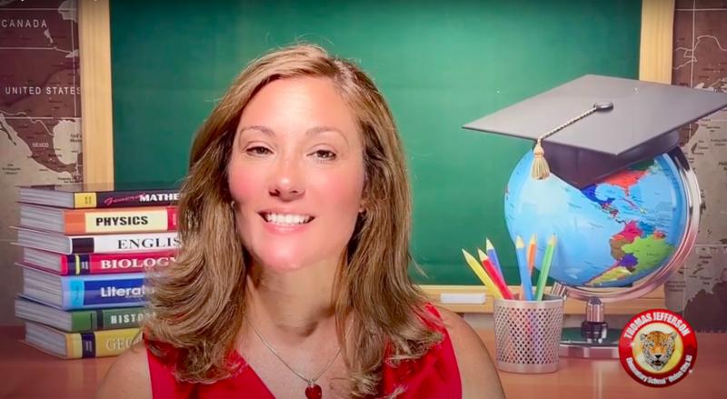 Woman speaking in front of teacher desk background