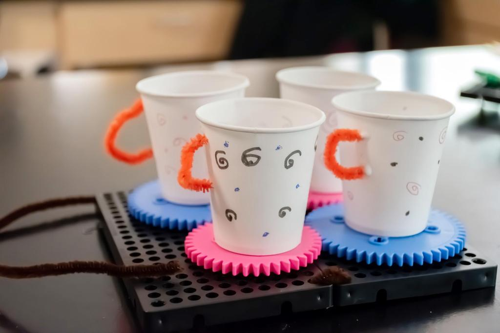 A kinetic sculpture featuring gears and four paper cups