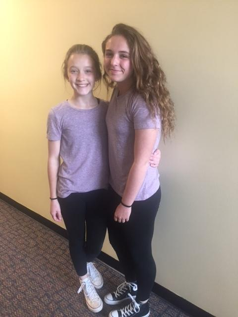 two girls in purple shirts smile for camera