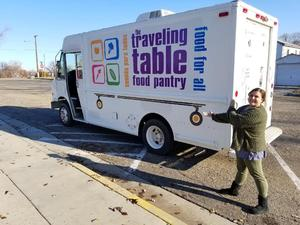 A student points to the Traveling Table delivery truck.