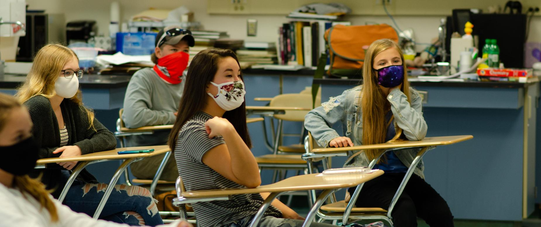 students at their desks wearing masks