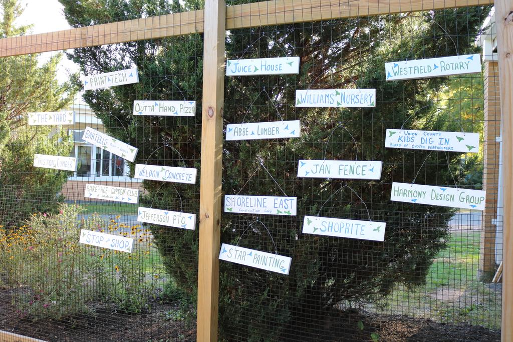 Photo of fence with signs of various contributors to Jefferson School garden/outdoor classroom.