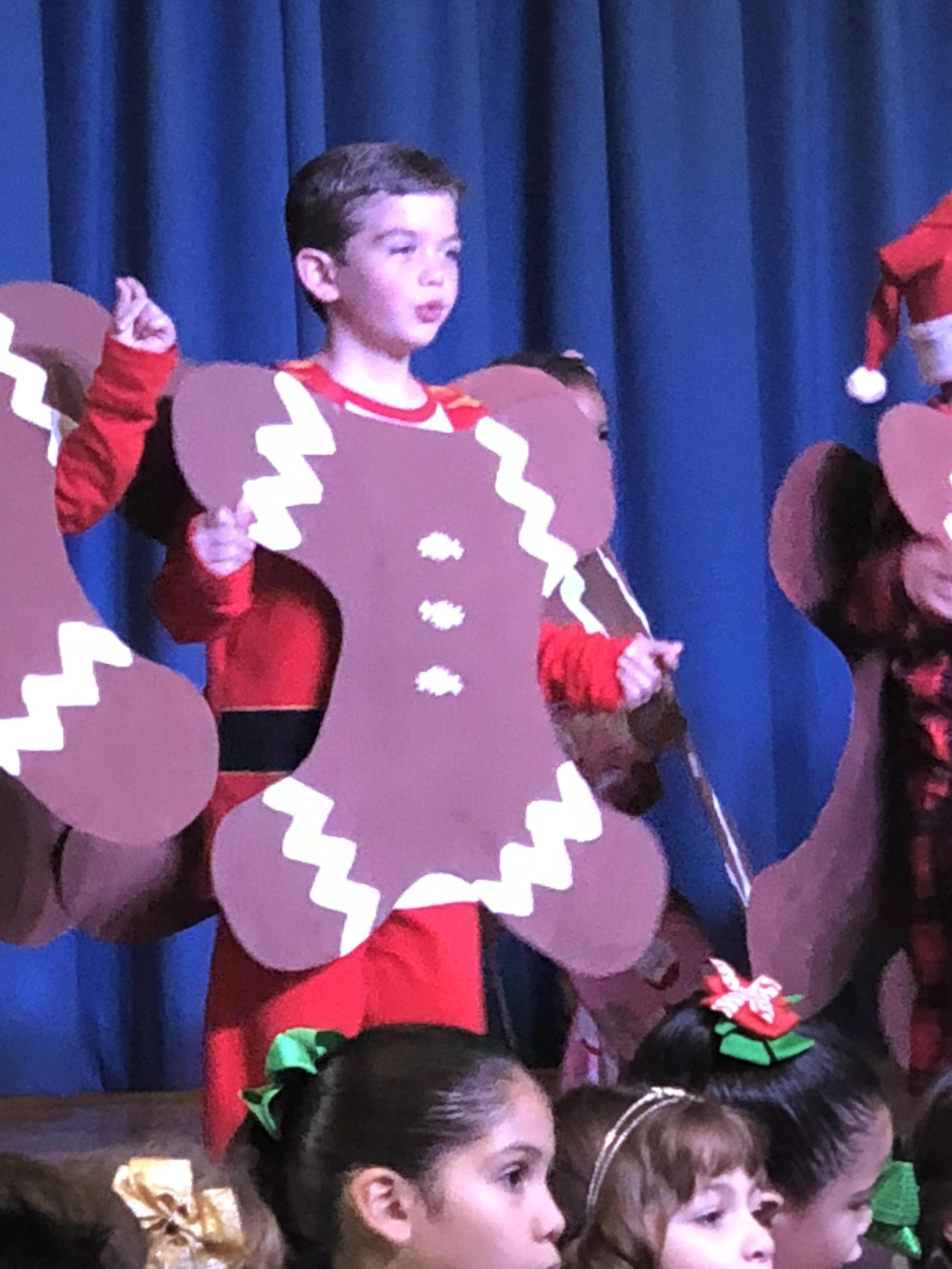 A little boy dressed as the gingerbread man.