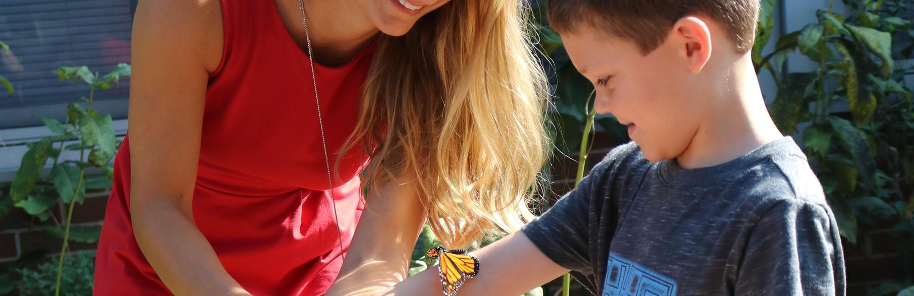 Tamaques 1st grader looks on with delight as a Monarch butterfly perches on his arm.