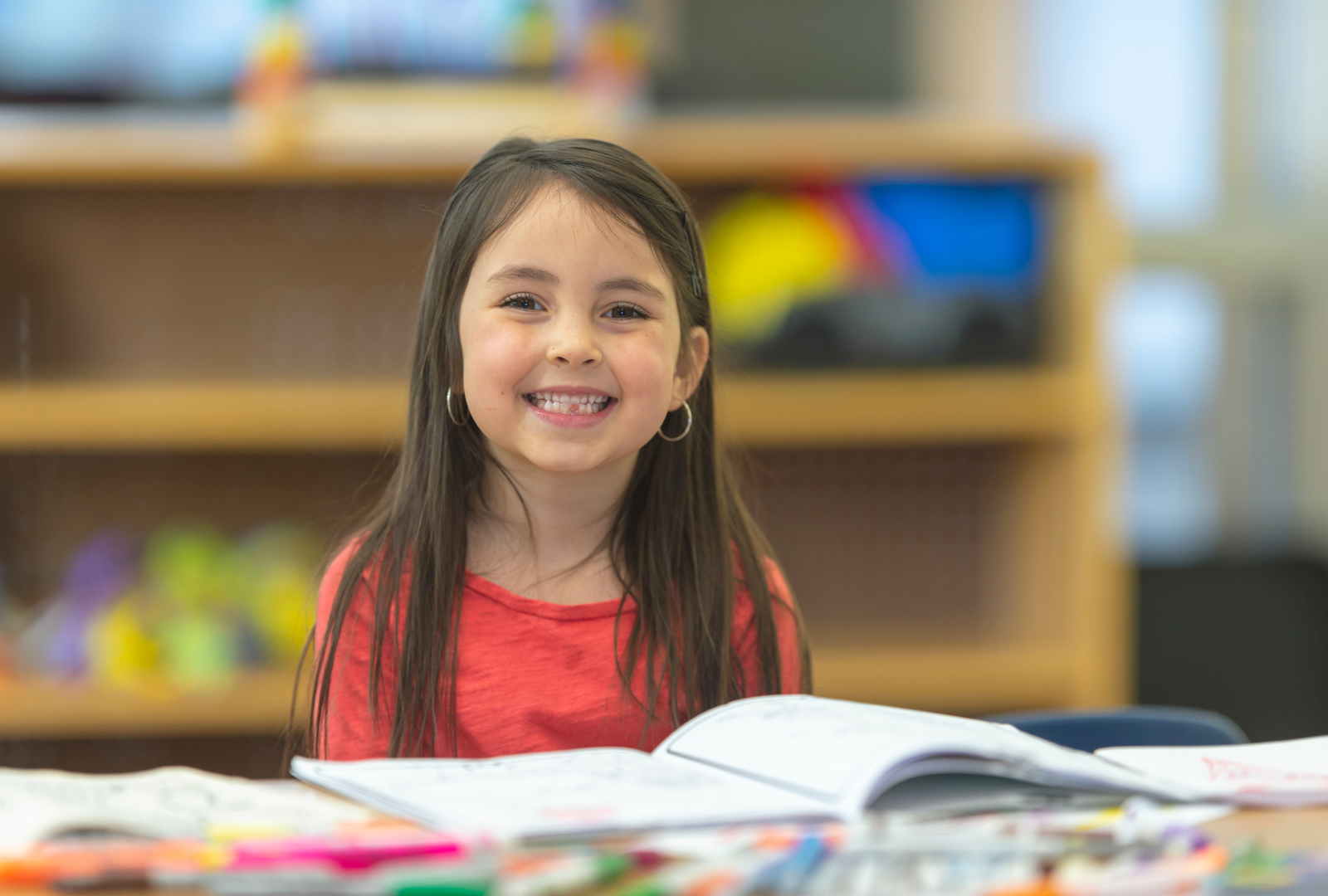 girl smiling in classroom with book in front of her