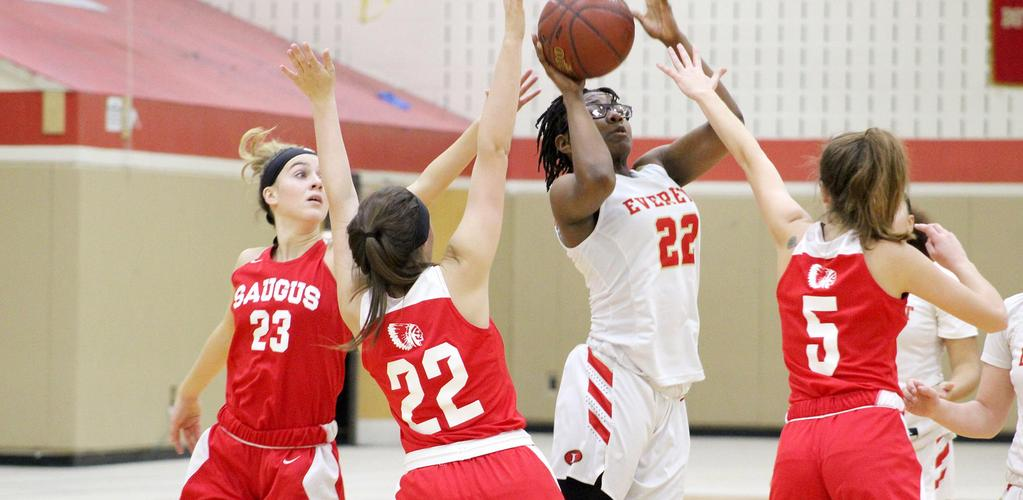 An EHS player is surrounded by three Saugus players as she drives to the basket