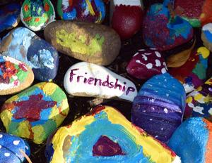Rocks painted with designs and one with the word