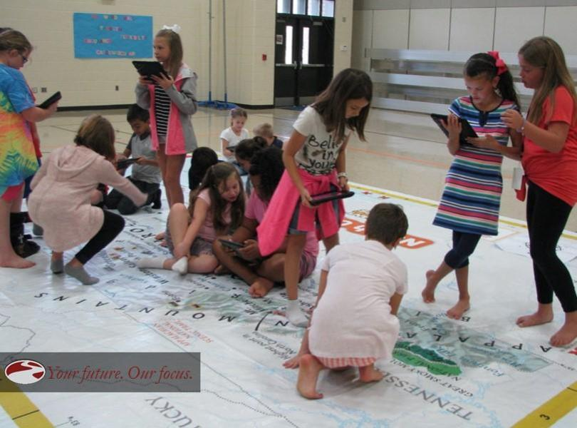 Picture of students doing a map activity with caption
