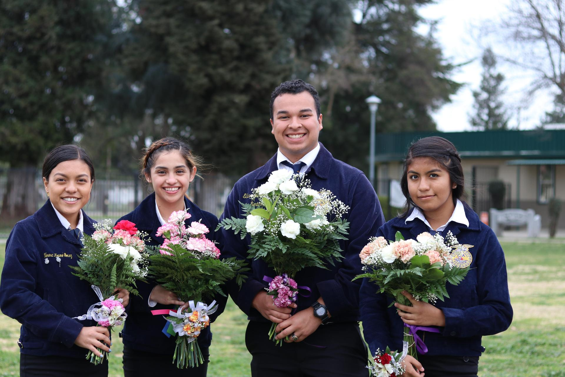Students pose with flowers before FFA award ceremony.