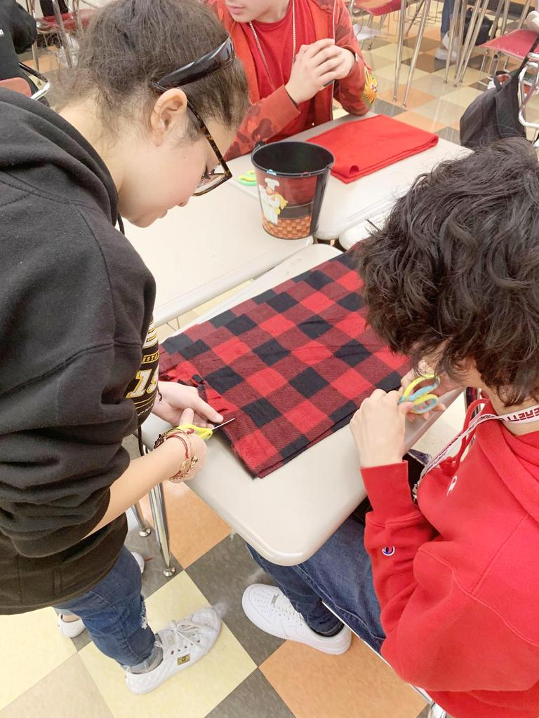 Students cut the red fabric used to make scarves for Brandon Conde Day