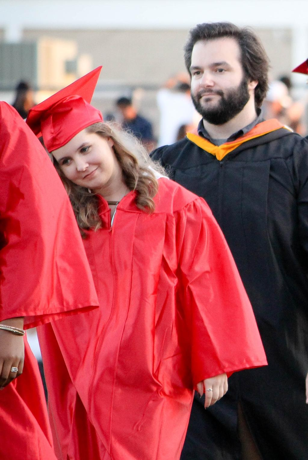 students of the victoria east high school 2018 graduating walking into memorial stadium, smiling female student and male teacher