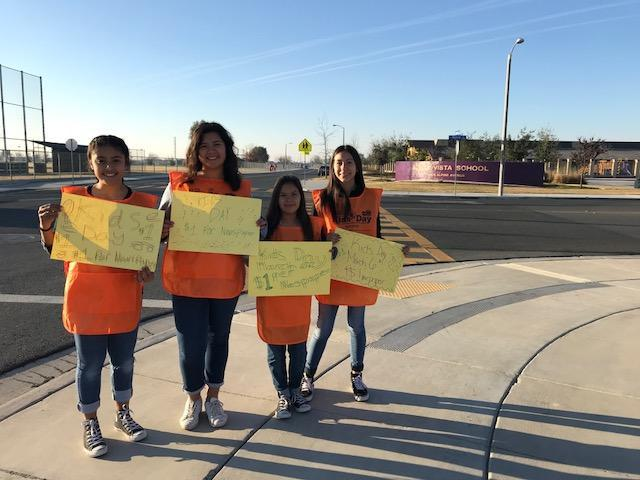 Girls holding welcome signs