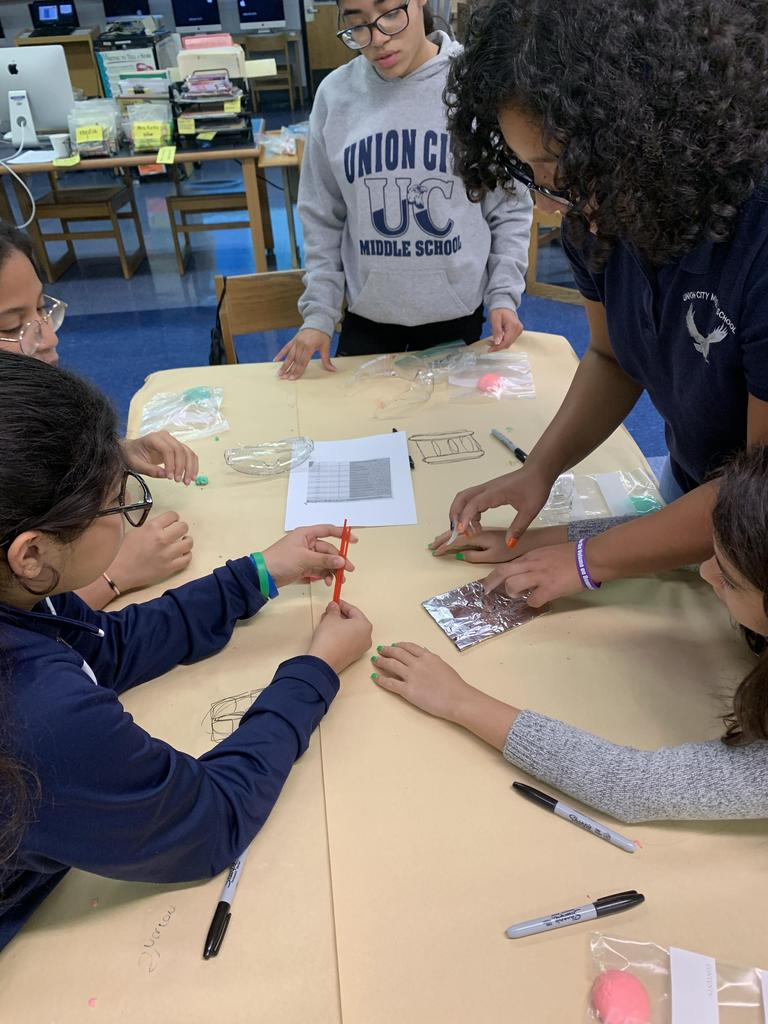 girls using pipe cleaners with aluminum foil to create a display