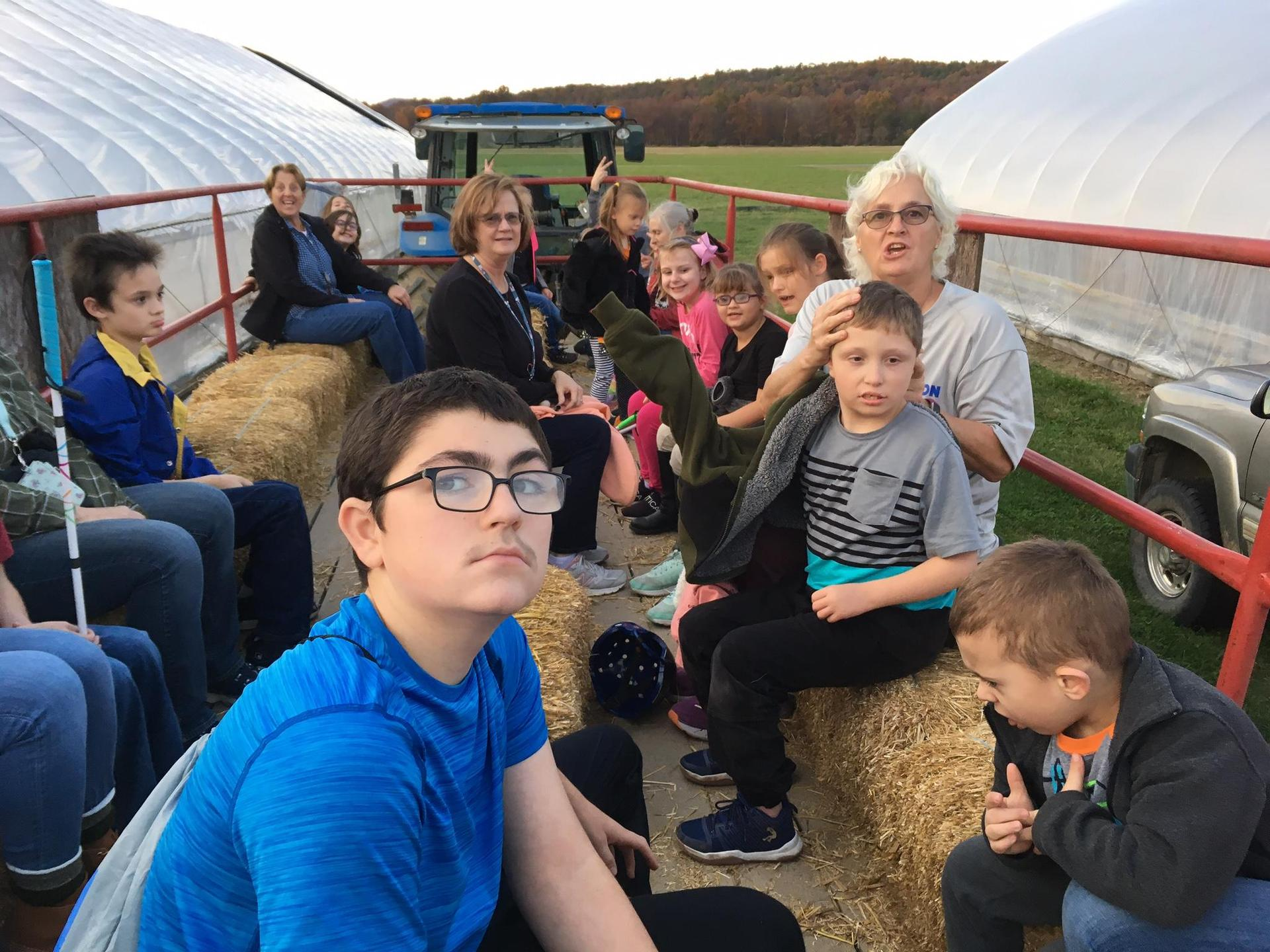 Dorm students facing the camera for a picture on the hayride