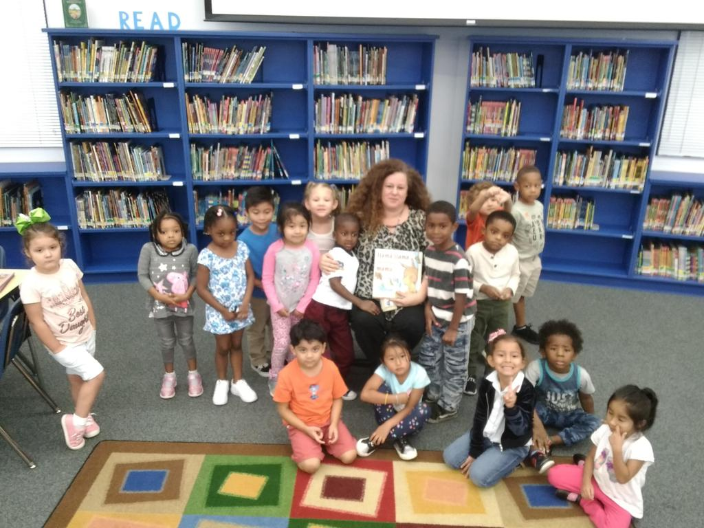 Pre-K students sitting with Mrs. Arizpe in the library