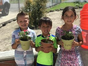 Students smiling with planted pots
