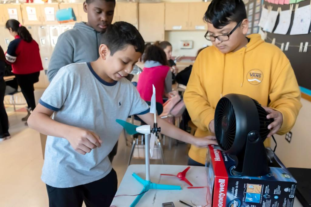 Three Keverian students experiment with a wind turbine they designed