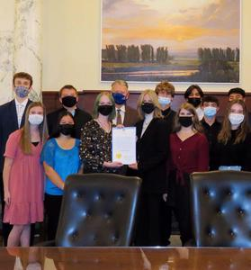 A close crop of the students posing with the governor and the proclamation at the Statehouse governor's office.